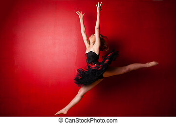 Young ballerina executing a jump against bright red wall -...