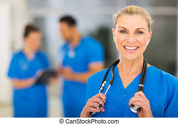 mid age female nurse - cheerful mid age female nurse in...