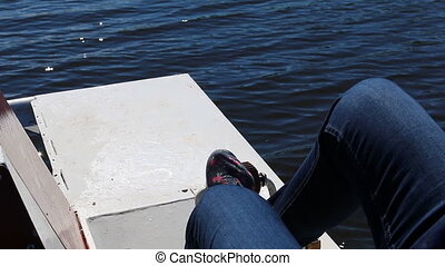 Pedaling pedal boat - Close up of legs of a girl wearing...