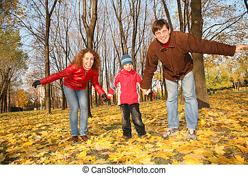 father and mother with the son in the park in autumn
