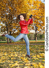 girl in the red jacket jumps in the park in autumn