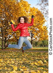 girl in the red jacket jumps in the park in autumn 2