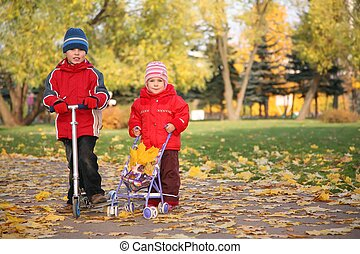 boy on the scooter and girl with the baby carriage in the park in autumn