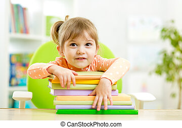 Cute child girl preschooler with books indoor
