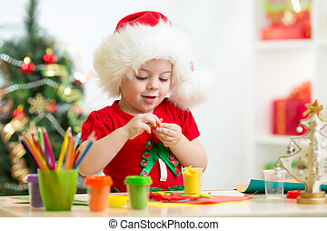 child making by hands christmas decorations - child girl...
