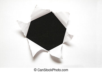 the sheet of paper with the hole against the black...
