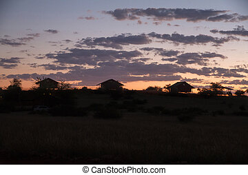 African village - Sun dropping down the hill in a african...