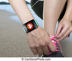 female hand tying shoelaces wearing bright green watchband...