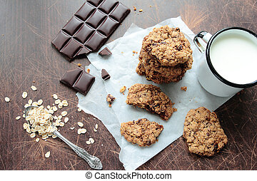 Crunchy oat cookies with dark chocolate and mug of fresh...