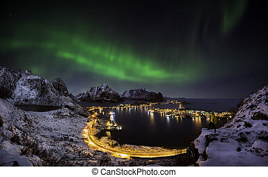 Northern lights over Reine, Norway - A man looking at the...
