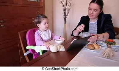 Happy baby girl eating and watching electronic tablet