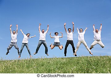 Seven friends in white T-shorts joyfully jump together