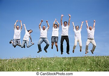 Seven friends in white T-shorts jump together
