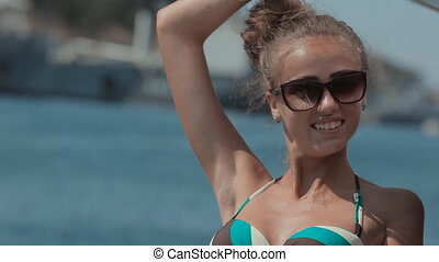 Young girl in bikini driving on a yacht by the sea