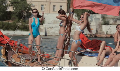 Beautiful slender girls having fun on a yacht that sails on the sea