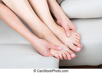 Woman legs and hands - Woman sitting on sofa, close up view...