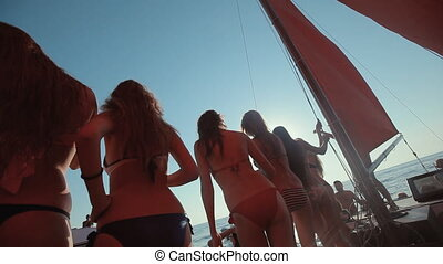 Girls in bikini and with a good figures having fun on a yacht with red sails