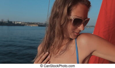 Beautiful girl in a white bikini with rhinestones enjoying life, smiling on a yacht