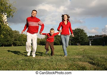 father and mother run, holding son for the hands