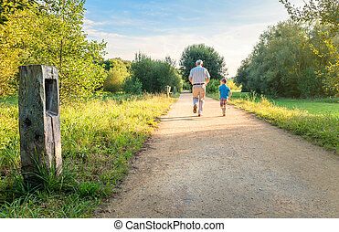 Senior man and happy child running outdoors - Back view of...