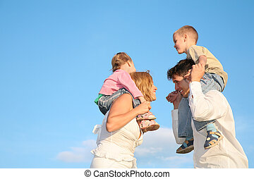 father and mother with the children on the shoulders 2