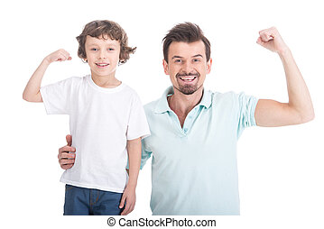 Father and son are showing biceps and smiling on white...