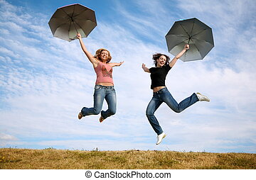 two young women jump with the umbrellas