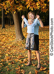 mother holds son for the hands in the park in autumn