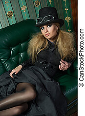 Beautiful blonde in a gothic gown. sitting on a leather...