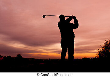 Golfer at Sunset - a golfer silhouetted in the sunset
