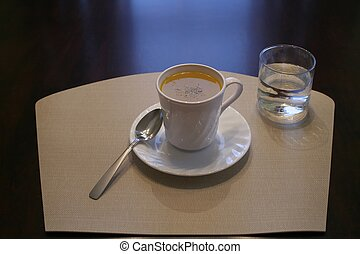 Soup Lunch - A cup of soup and a glass of water on a...