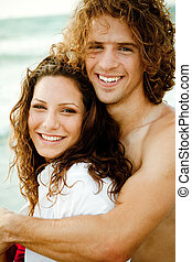 Teen couple embracing - Romantic teen couple smiling and...