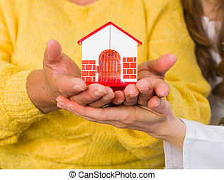 Home protection - Women holding in hands a miniature house