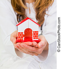 Home care - Young woman holds in her hands a plastic house