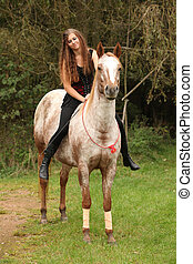 Pretty girl riding a horse without any equipment in autumn