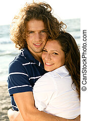 At the beach - Young guy and lady smiling at camera while...