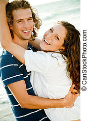 Couple at the beach smiling - Young couple facing camera and...