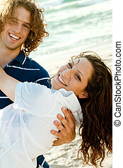 Couple having fun - Young teen holding lady in his arms as...