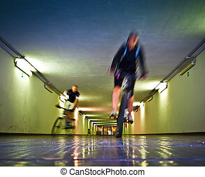 Two bikers in a tunnel - Motion blur of two bikers riding in...
