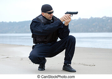 security man - The security man aim at something with gun.