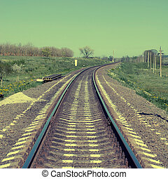 square toned image of railroad recedes into the distance,...