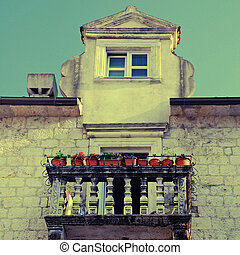 balcony with flower pots in old european town - balcony with...