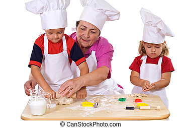 Grandmother teaching kids how to make cookies - Grandmother...