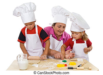 Grandmother teaching kids making cookies - Grandmother and...