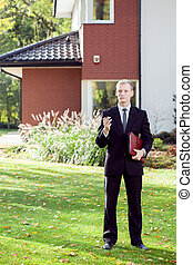 Elegant house agent wearing suit - Vertical view of elegant...
