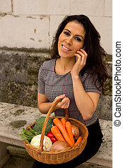 young woman holding a basket of vegetables on the phone.