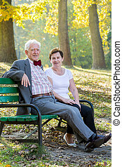 Elegant couple - Elegant older couple resting in park