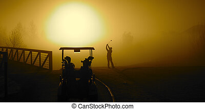 Golfer in the Golden Sunrise fog on a misty morning with a...