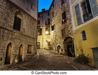 Narrow cobbled street in old town Peille at night, France