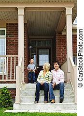 Happy family at home - Young family sitting on front steps...